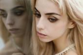 Portré egy gyönyörű szőke lány. Reflexió a tükörben.