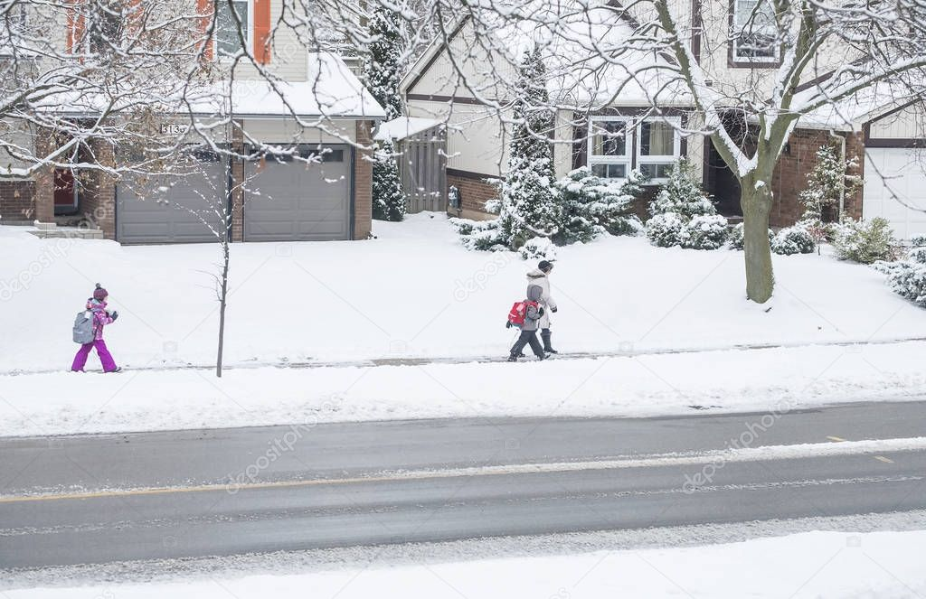 Mississauga, Canada - December 12, 2017: An Adult Walking Children to the School in the Early Morning in Snowy Weather (Editorial)