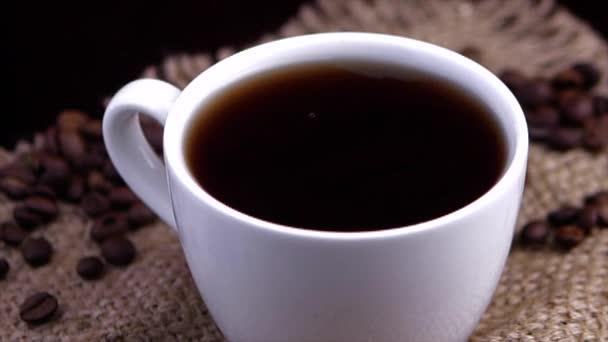 fehér bögre kávé és kávébab heverészik, közeli kávécseppek esnek egy pohárba. lassított felvétel