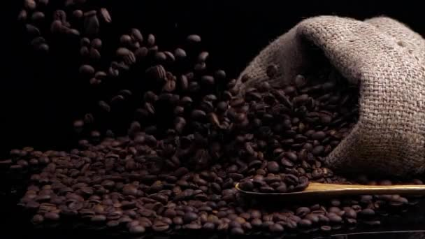 Composition from coffee beans. Black background decorated with bag with coffee beans, scoop with fragrant coffee beans. Slow motion