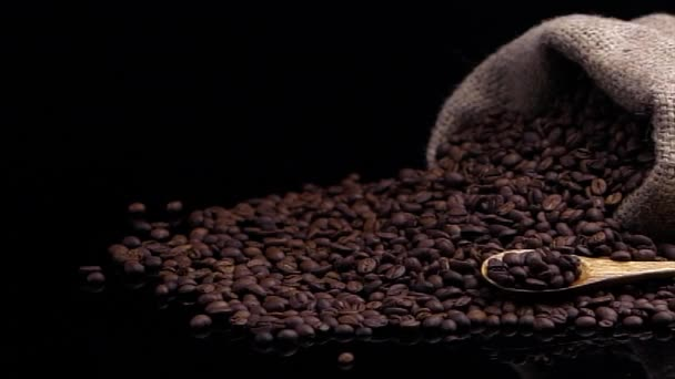 Kávová zrna s pytlem a lžičkou. Ve zpomaleném filmu