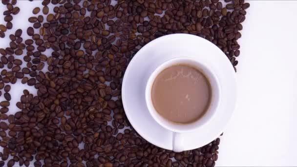 Šálek kávy a kávová zrna. Bílý šálek. Záběry