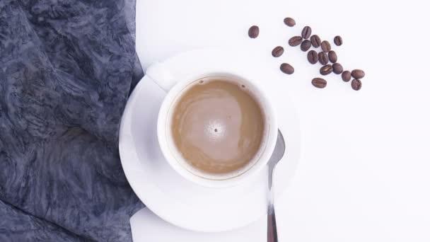 Šálek kávy zblízka. Kávová zrna. Zpomalený výstřel. Záběry