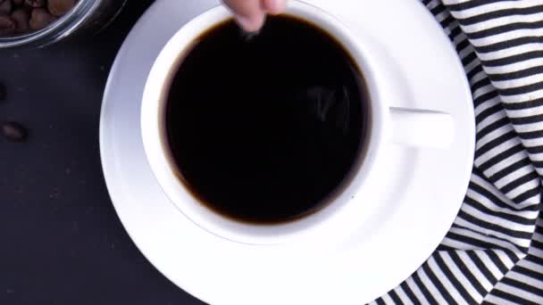 Top view of person hand stirring coffee with spoon