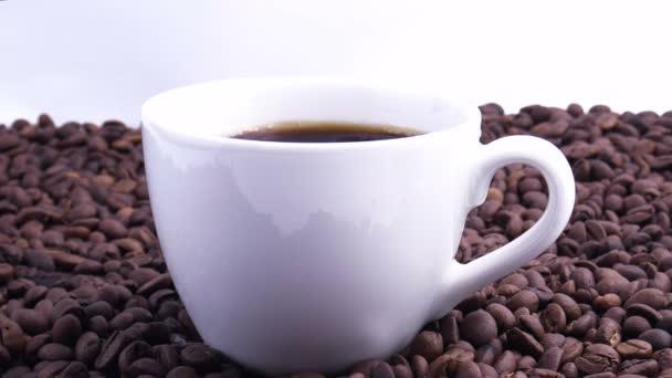 Kávécsésze és kávébab. Egy csésze fehér kávé az asztalon sült babbal. Lassú mozgás.