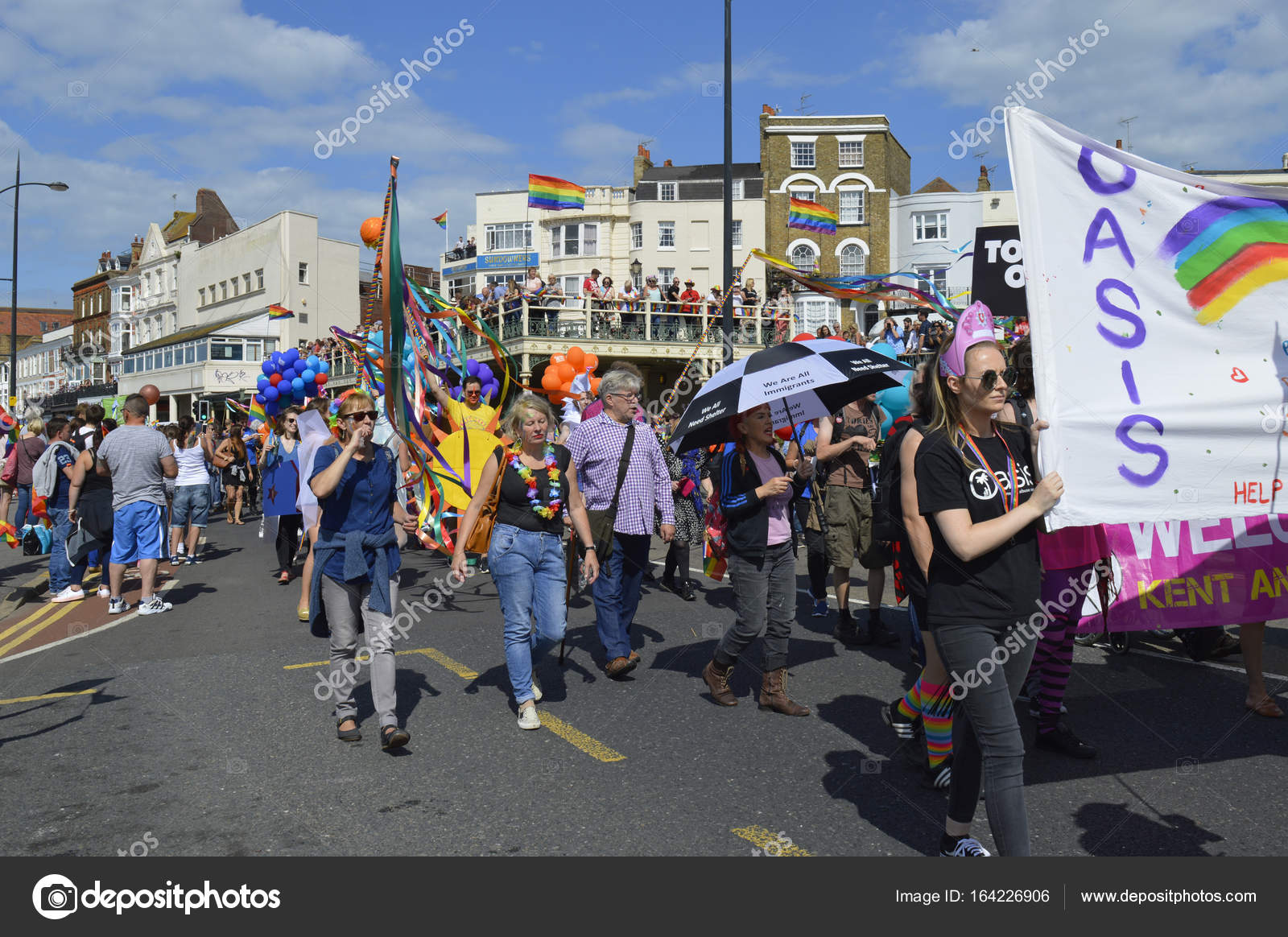 People carrying flags and banners marching in the colourful Gay