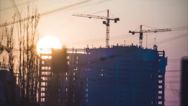 Západ slunce opouští pro mrakodrap ve výstavbě s pohyblivými jeřáby