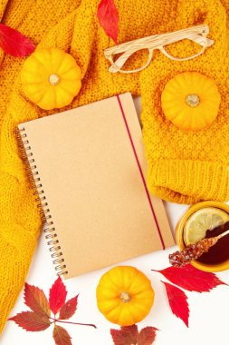 Flat lay autumn composition with fall leaves, hot cup of tea and a warm woolen orange sweater
