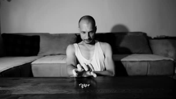 Depressiver Mann, der an selbstmörderischer Depression leidet, will Selbstmord begehen, indem er starke Medikamente und Tabletten nimmt, Schmerzmittel nimmt und in seinem dunklen Zimmer sitzt, selektiver Fokus launisch-dramatischer Blick