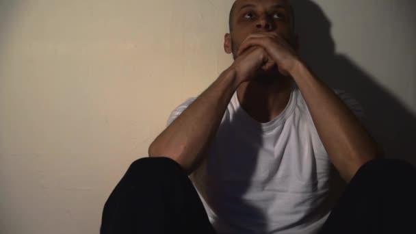 Magányos és depressziós függő férfi ül egyedül a padlón a sötét otthon érzés nyomorult és nyugtalan sötét felvételek társadalmi dokumentumfilm egészségügyi koncepció