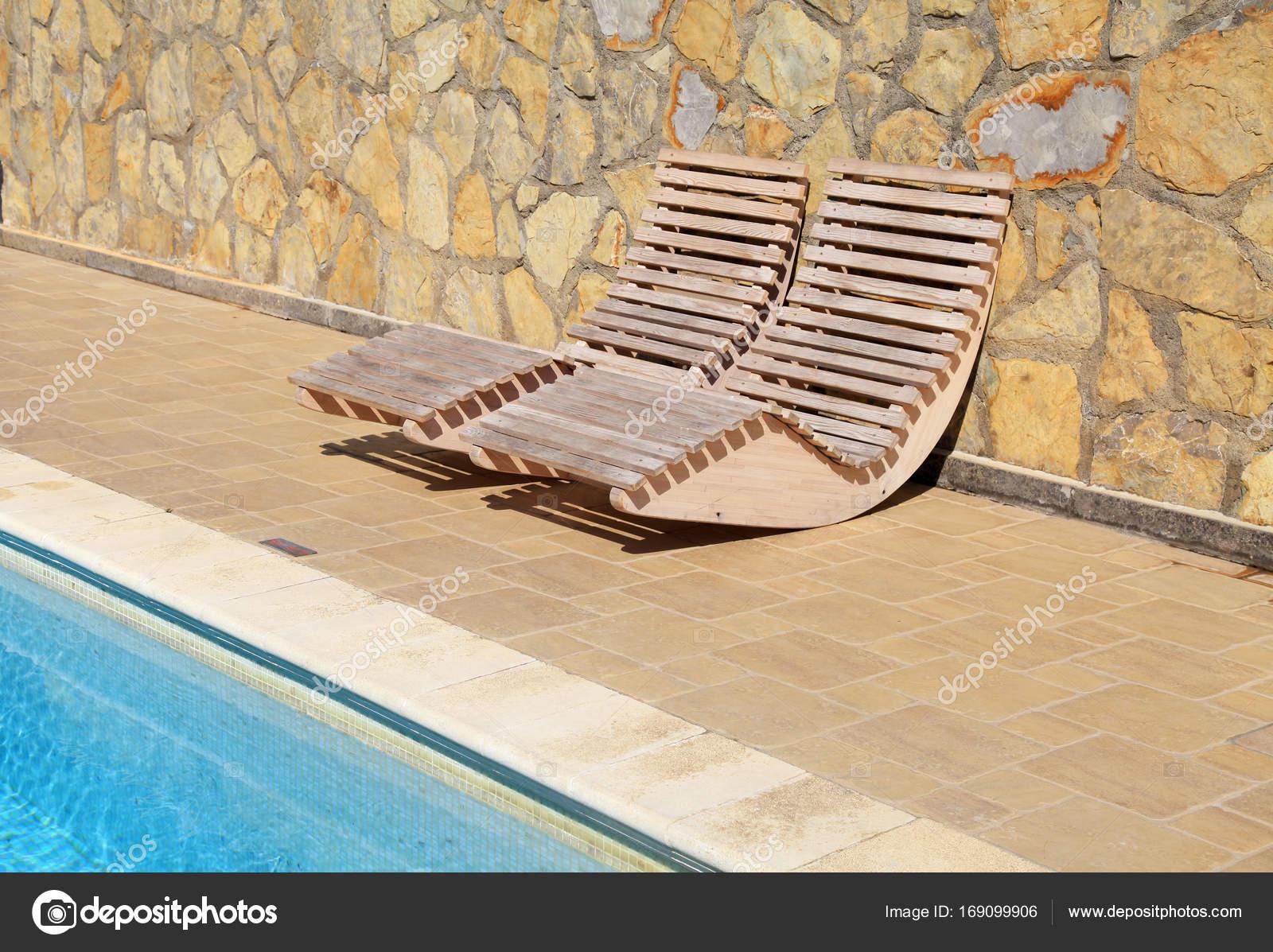 Buiten hout ligbedden op resort zwembad terras u stockfoto