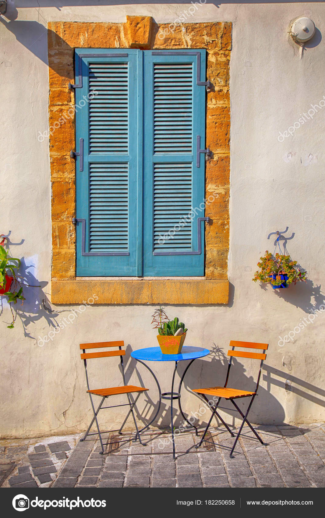 Blue Shutters Window And Small Chairs Andtable On Sidewalk