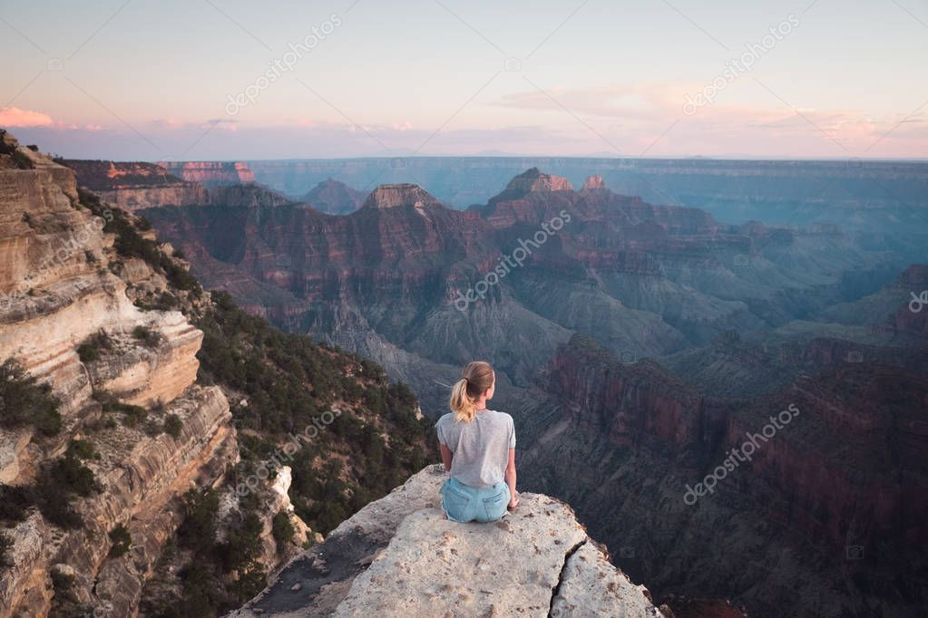 Blonde woman sitting on edge of cliff and enjoying scenic view of mountain landscape
