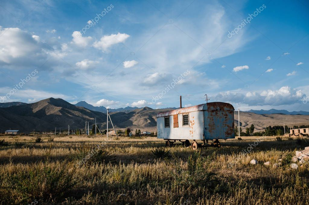 Landscape in Kyrgyzstan mountains with abandoned trailer on meadow