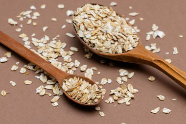 oat flakes in a two wooden spoon on a brown background