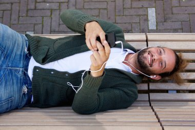 Happy man lying down on bench listening to music
