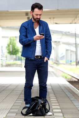 Man using mobile phone at train station