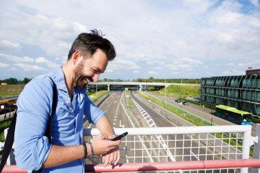 Mature man on the bridge using mobile phone