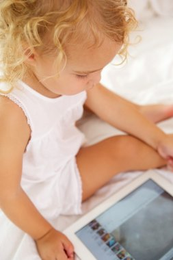 Girl sitting on bed with digital tablet