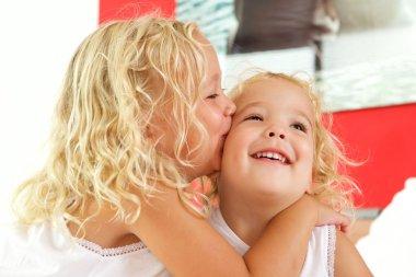 Little girl kissing her sister