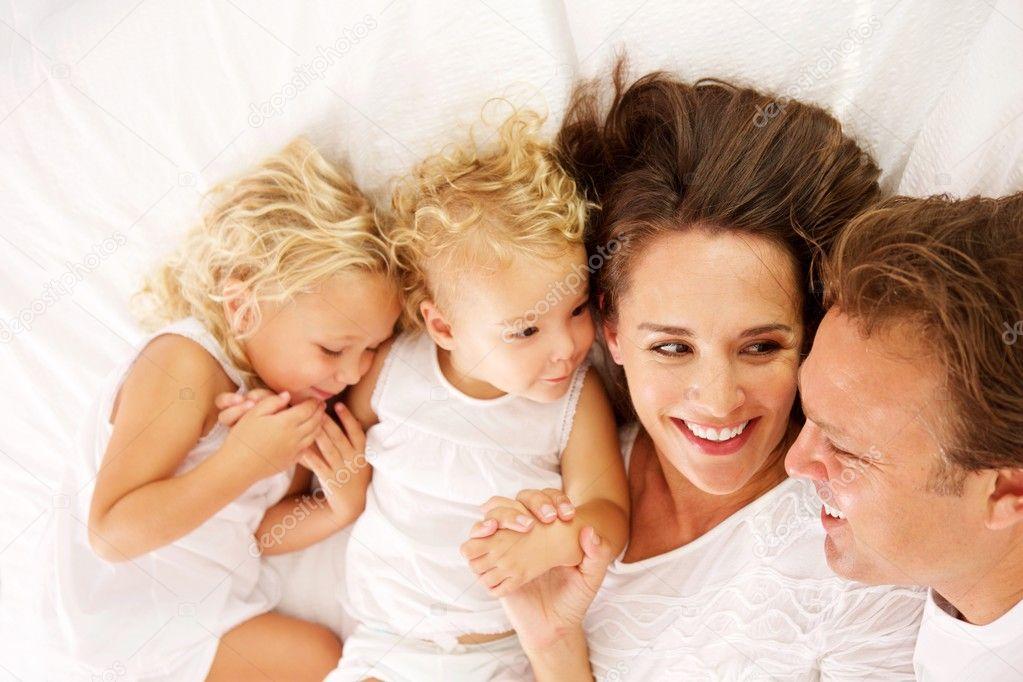 Familia Feliz Acostado Juntos En La Cama