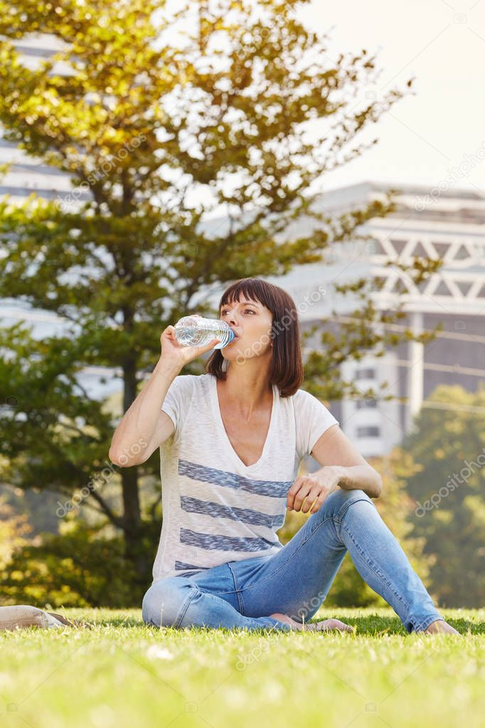 Woman drinking water at park