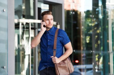 guy walking with bag while he talking on cell phone