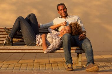 Portrait of beautiful laughing couple sitting on park bench outside