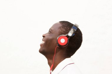 Close up side portrait of smiling man listening to music with headphones on white background