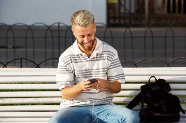 Portrait of smiling young man sitting on bench listening to music on smart phone