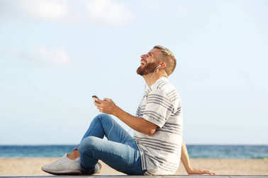 Portrait of happy young man sitting by beach listening to music with mobile phone and earphones