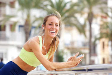 Portrait of happy young woman listening to music with smart phone