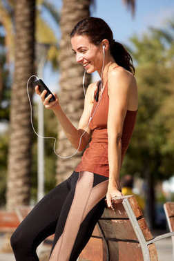Portrait of healthy young woman standing outdoors and listening music on her mobile phone