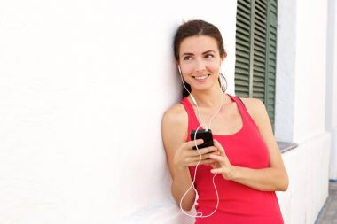 Portrait of beautiful female athlete standing by a wall with earphones and mobile phone