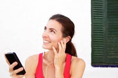 Close up portrait of fit young woman relaxing with mobile phone and earphones after workout session
