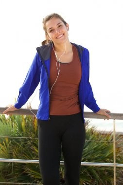 Portrait of cheerful athlete standing outside with earphones after workout