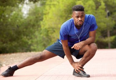 Portrait of fit young african american man doing stretching exercise while listening to music with earphones