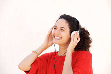 Close up portrait of beautiful young woman listening to music with headphones against white background
