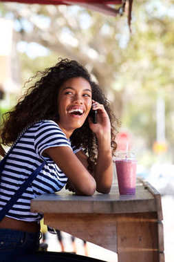 Portrait of happy young africana american woman laughing and talking on smartphone at cafe