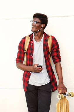 Portrait of happy young black man standing with mobile phone and skateboard