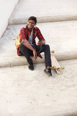Portrait of happy african american guy sitting outside on steps with mobile phone and skateboard
