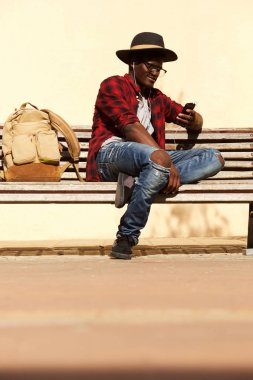 Portrait of stylish young african man sitting on bench using smart phone
