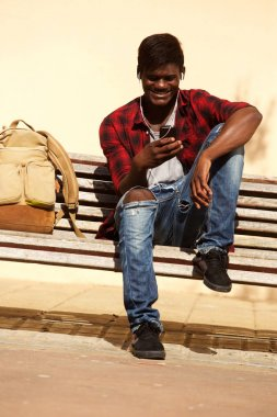 Portrait of african male model sitting on bench using cell phone