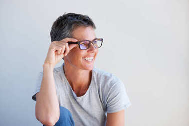Close up portrait of beautiful older woman smiling with glasses against white background