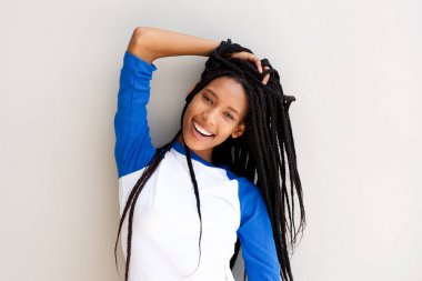 Portrait of attractive young black woman with braided hair posing against a wall