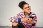 Portrét šťastné mladé africké americké dívky sedící s mobilním telefonem