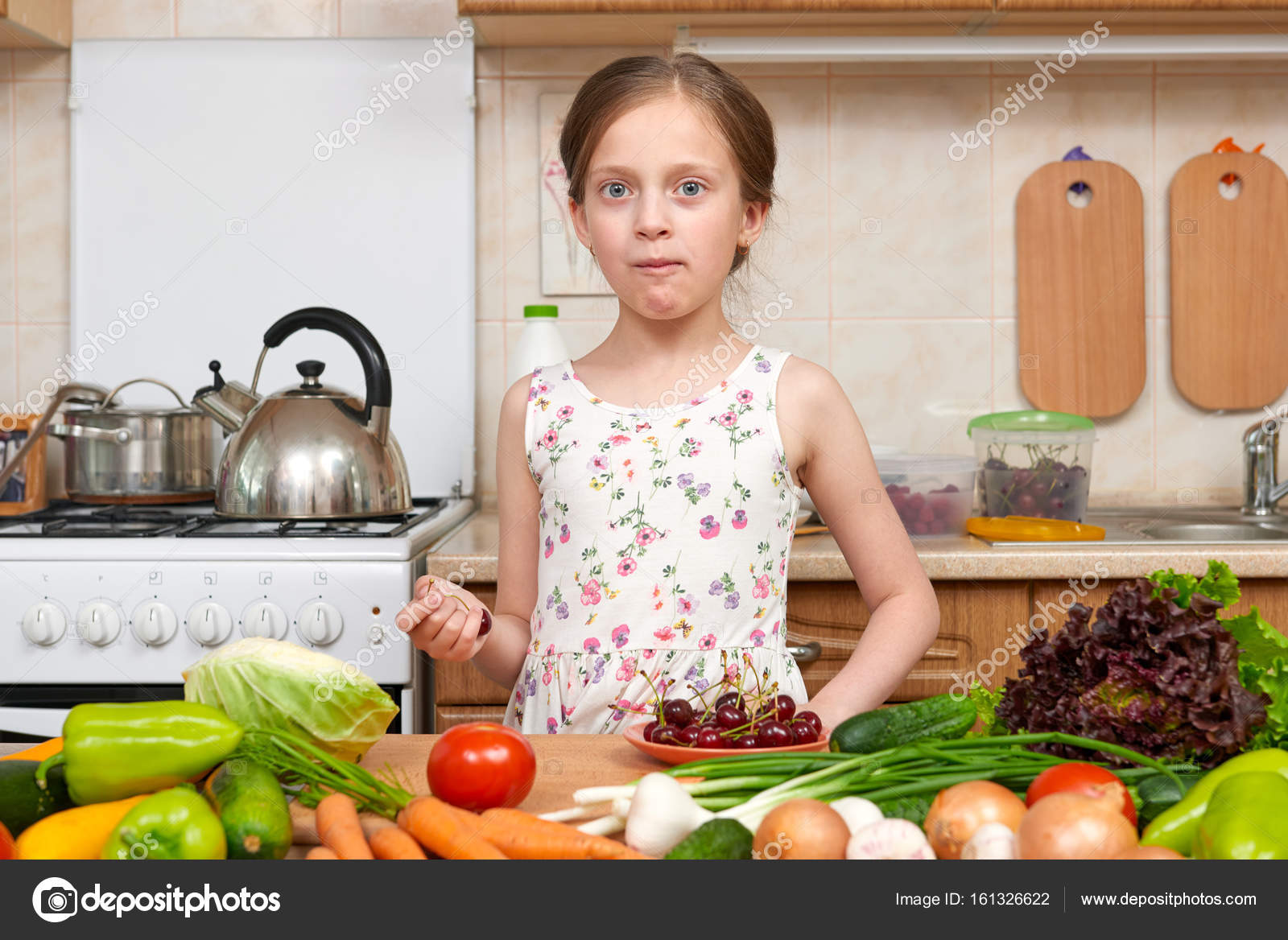 muchacha del niño comer cerezas, frutas y verduras en la cocina ...