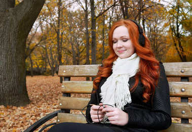 Young woman portrait in autumn park, listening to music on headphones