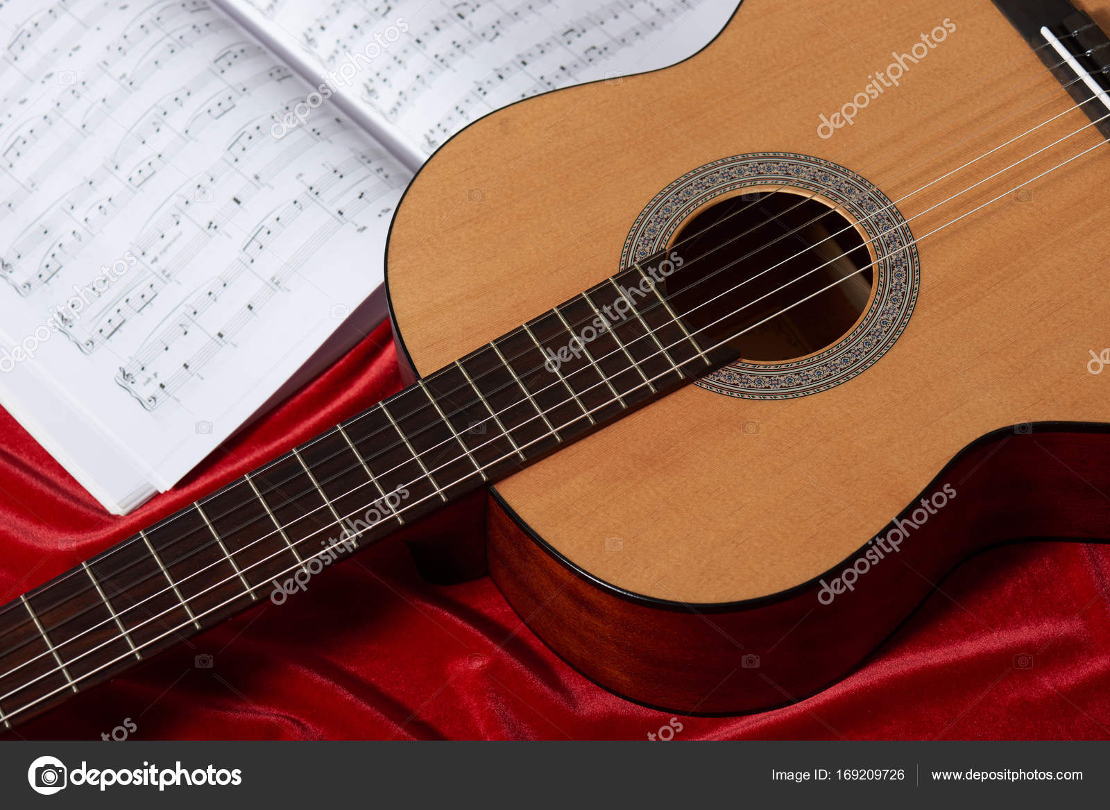 Acoustic Guitar And Music Notes On Red Fabric Close View Of Obj