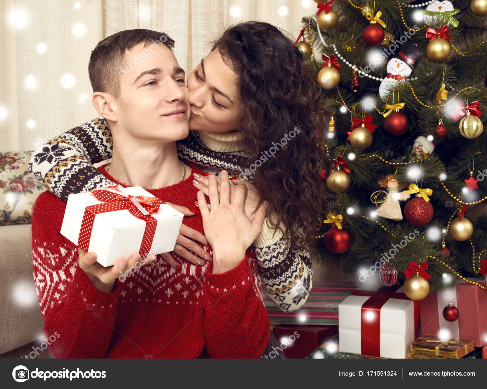 Happy couple kiss in christmas decoration at home. New year eve ...